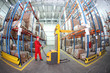 worker in red uniform at work in warehouse - fish eye lens