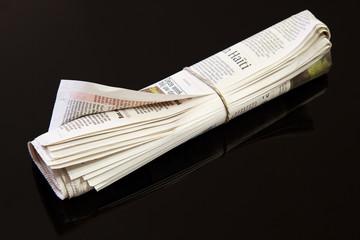 rolled up newspaper on black