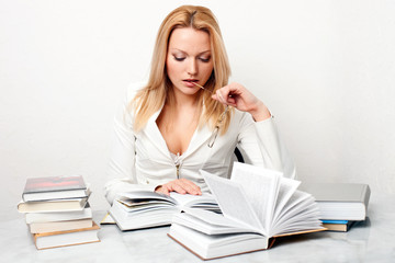 Young woman holding glasses at table with books