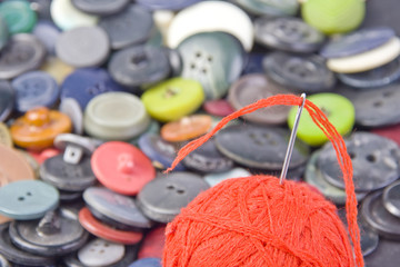 Sewing needle in ball of threads with buttons on background
