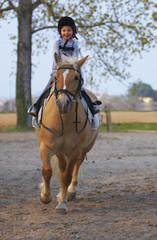 Bambina di tre anni cavalca ridendo pony