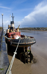 Old tug boat moored by the side of a river