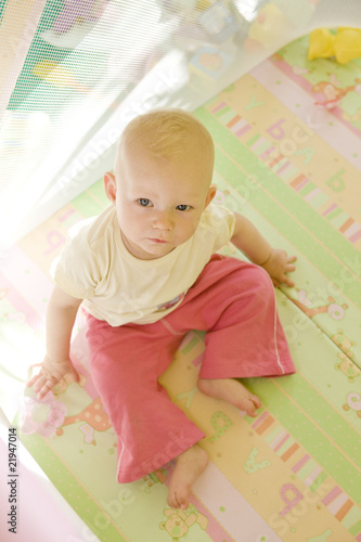 toddler sitting in cot