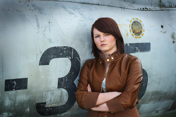Pretty teenage girl leaning against disused military plane