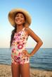 Preteen girl in straw hat enjoying sunbath on sea beach