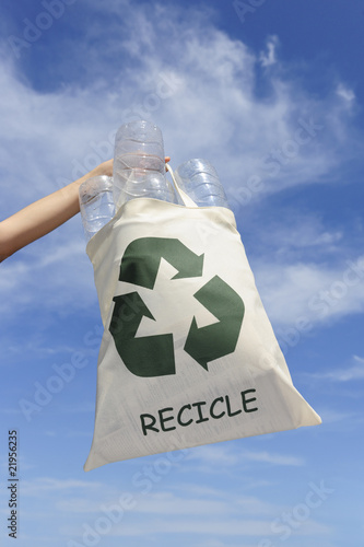 recycling: hand holding bag with plastic bottles