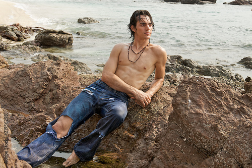 Muscular man laying on the rocks on the beach.