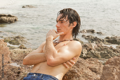 Young man resting on ocean rocks, hair wet from swimming.