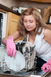 Young woman using a dishwasher