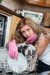 Tired cute woman filing the dishwasher