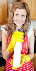 Beautiful blond woman holding a detergent spray