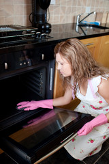 Tired woman cleaning the oven