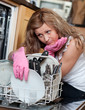 Tired young woman filing the dishwasher