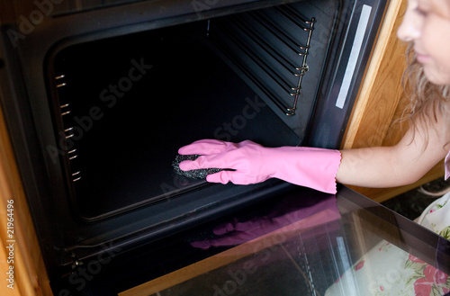 Close-up of a woman cleaning the oven