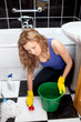 Caucasian young woman cleaning bathroom's floor