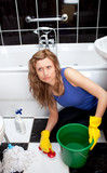 Unhappy woman cleaning bathroom's floor