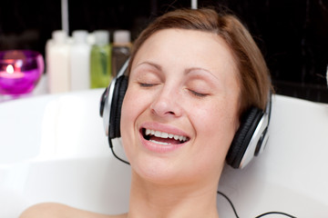 Smiling young woman listening music  in a bubble bath