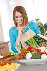 Cooking - Smiling woman holding coobook, with vegetable and past