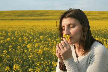 Beautiful woman in field with yellow flowers.
