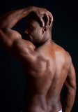 Strong black man showing off his back