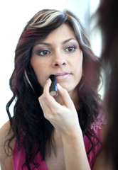 pretty young woman applying mascara./eyeshadows in front of a mi