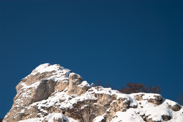 Snow-covered high rocky cliff against clear blue sky