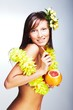 Beautiful girl with Hawaiian accessories drinking grapefruit