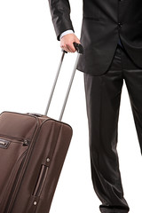 Business traveller with a suitcase (focus on the suitcase)