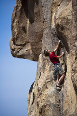 Male rock climber reaching for the summit.