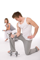 Fitness - Young healthy couple exercise with metal weights