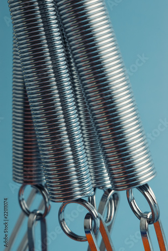 Pulling down twisted metal coil springs on blue background