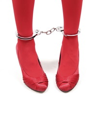 Restraint. Woman red legs in handcuffs