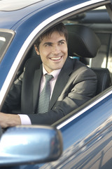 Smiling businessman driving car