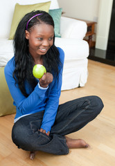 Jolly woman eating an apple sitting on the floor
