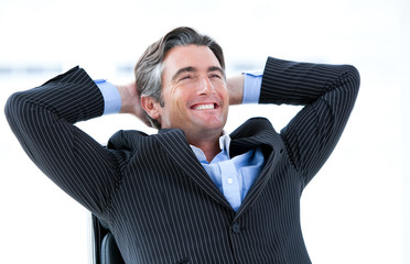Laughing male executive thinking about his success