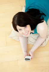 Relaxed woman listening music lying down on the floor