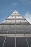 Triangular office business building against blue sky poster