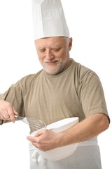 Senior chef whisking egg in kitchen