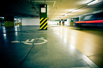 Parking garage, underground interior with car in motion blur