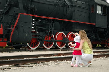 Woman with child beside locomotive
