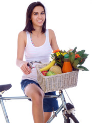 smiling girl riding a bike with basket of fresh fruits & flowers