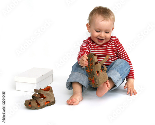 Baby and shoes - child tries to put on shoes