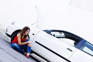woman waiting seated by next to her car