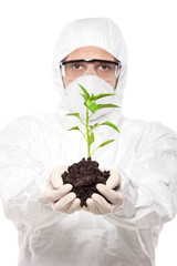 A man in uniform holding a peper plant isolated on white