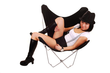 Asian girl lying in a butterfly chair.