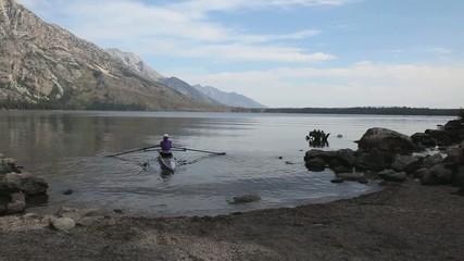 Person Rowing a Kayak on Lake