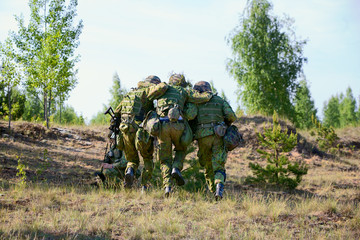 Two NATO Army soldiers escorted the wounded  soldier