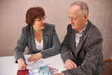 elderly couple at the table decide money issues poster