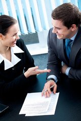 Businesspeople or business person and client, with document