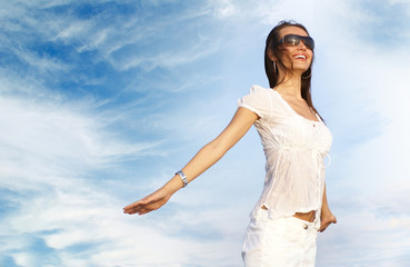 Young and happy woman on a cloudy background
